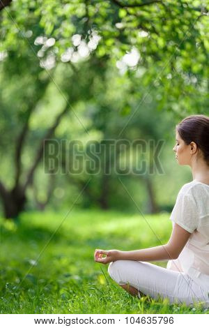 Young girl in lotus pose outdoors