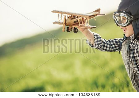 Boy with wooden airplane in the field