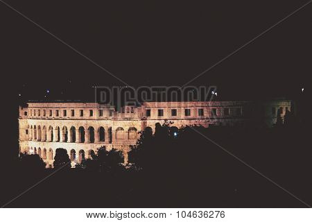 Ancient amphitheater in Pula in Croatia at night, artistic toned photo