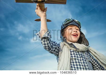 Happy boy with wooden airplane in the field