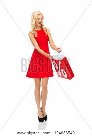 people, sale, discount and holidays concept - smiling woman in red dress with shopping bag