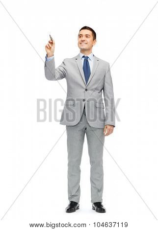 business, people and office concept - happy smiling businessman in suit writing or drawing something imaginary with marker