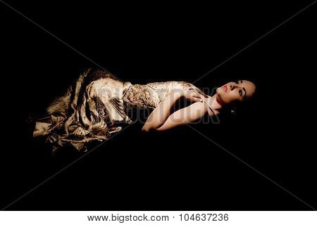 brunette woman in evening gown lying down