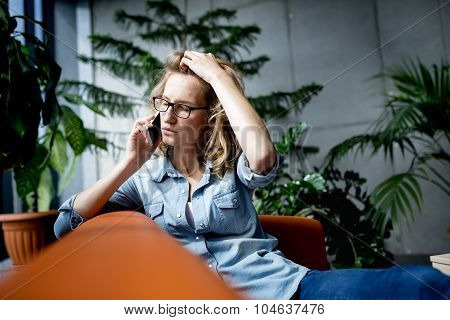 Beautiful young businesswoman using mobile phone while working with laptop in office.