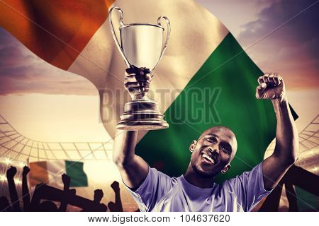 Happy sportsman looking up and cheering while holding trophy against large football stadium under cloudy blue sky