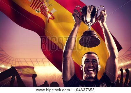 Portrait of successful rugby player holding trophy against large football stadium under purple sky