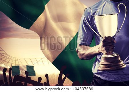 Mid section of sportsman holding trophy and rugby ball against large football stadium under cloudy blue sky