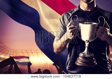Victorious rugby player holding trophy against large football stadium under purple sky