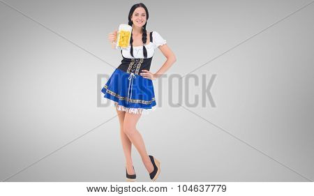 Pretty oktoberfest girl holding beer tankard against grey vignette