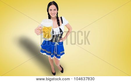 Pretty oktoberfest girl holding beer tankard against yellow vignette