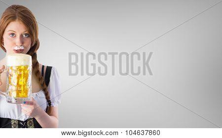 Oktoberfest girl drinking jug of beer against grey vignette