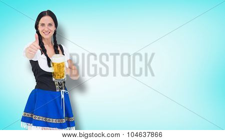 Pretty oktoberfest girl holding beer tankard against blue vignette background