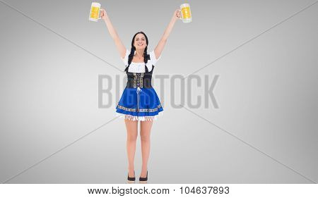 Pretty oktoberfest girl holding beer tankards against grey vignette