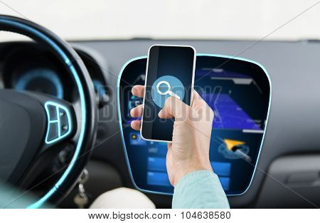 transport, business trip, technology and people concept - close up of young man hand driving car and holding smartphone with lens icon on screen