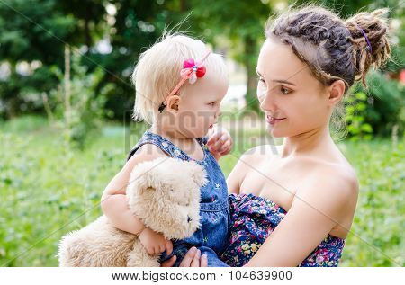 Mother hold her child on hands. Outdoor portrait