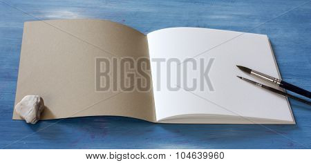 Open sketchbook with a blank white page, with two watercolor brushes, on blue background