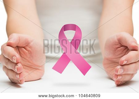 Hands presenting against pink breast cancer awareness ribbon