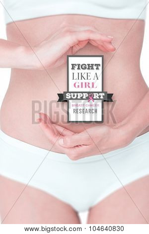 Woman with hands on belly against breast cancer awareness message