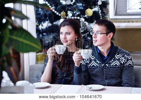 Young happy couple looking ine one side holding a cup. Christmas tree
