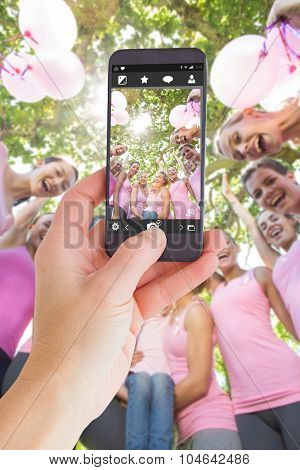 Female hand holding a smartphone against smiling women in pink for breast cancer awareness