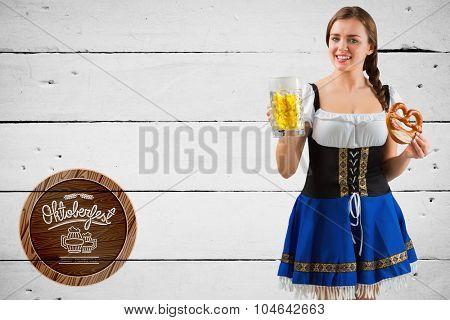 Oktoberfest girl holding beer and pretzel against white wood