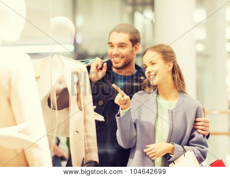 sale, consumerism and people concept - happy young couple with shopping bags pointing finger to shop window in mall