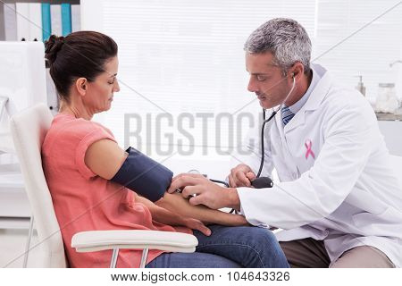 Pink awareness ribbon against doctor doing test at his patient