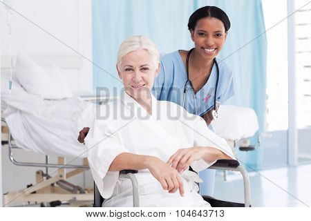 Portrait of smiling nurse with female patient in wheelchair against pink awareness ribbon