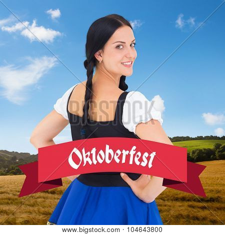 Pretty oktoberfest girl smiling at camera against country scene