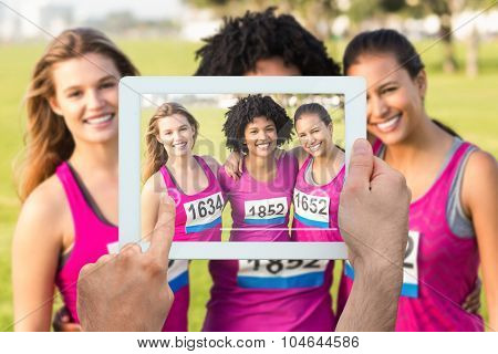 Hand holding tablet pc against three smiling runners supporting breast cancer marathon