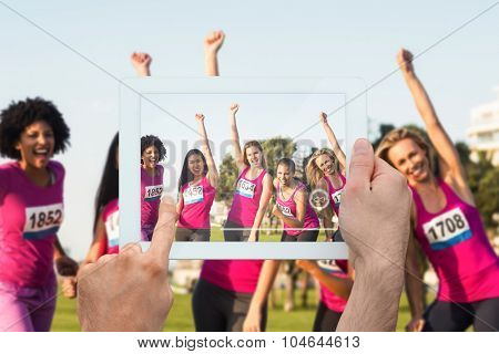 Hand holding tablet pc against cheering women supporting breast cancer marathon