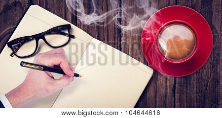 Overhead view of hot tea by hand writing on book against wooden table