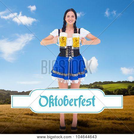 Pretty oktoberfest girl holding beer tankards against country scene