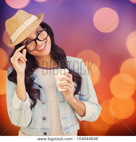 Brunette with disposable cup against glowing background