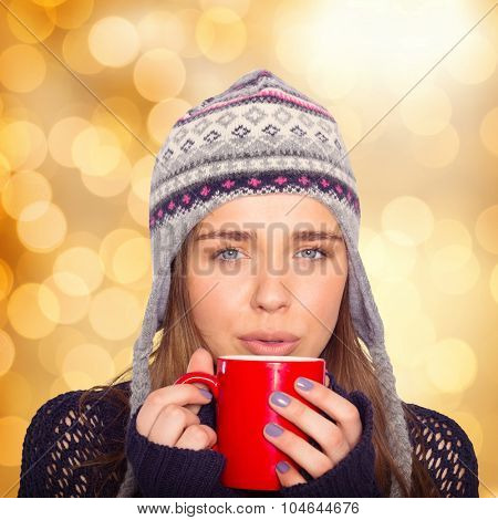 Beautiful woman in warm clothing drinking coffee against glowing background