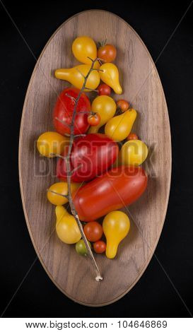Organic garden Red and yellow cherry tomatoes on a wooden bowl isolated on black