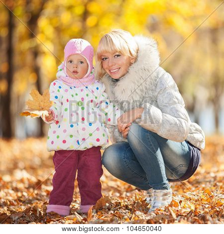 Mother and daughter in the autumn park