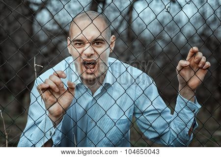 Angry And Fearful Man Grinning Over The Fence Mesh.