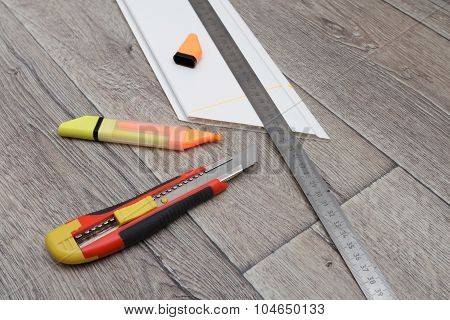 Home Improvement. Measuring And Cutting Process Of Plastic Panel On Wooden Floor.