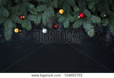 Christmas or New Year decoration background: fur-tree branches, colorful glass balls  on black grung