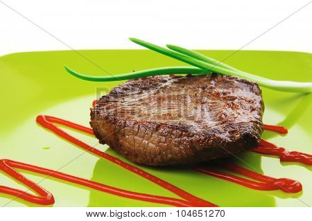 meat food : roasted fillet mignon on green plate with chives and ketchup isolated over white background