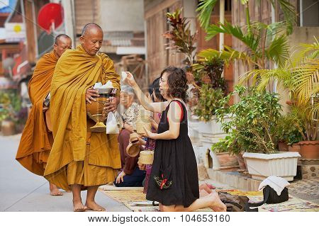 People offer sticky rice to Buddhist monks in the morning in Chiang Khan, Thailand.