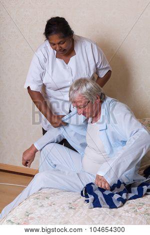 Nurse in nursing home helping elderly man getting dressed