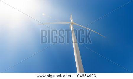 Power generating wind turbine on blue sky with bright sun rays