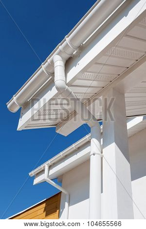 New rain gutter on a white home against blue sky