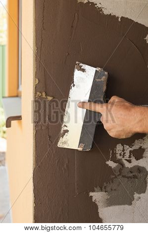 Man hand with trowel plastering a house wall