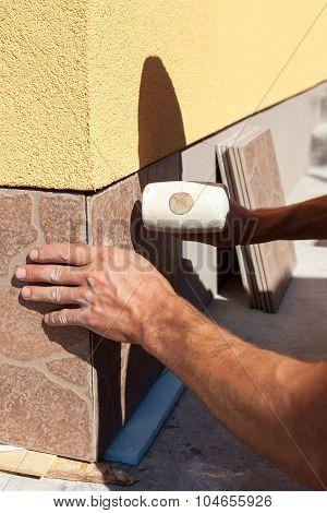 Industrial tiler builder worker installing tile on the wall
