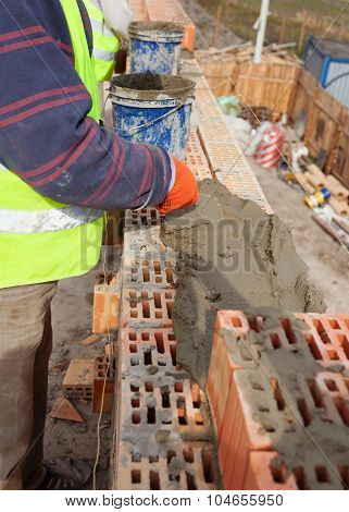 Worker building brick walls at house construction site bricklayer and cement