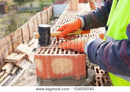 Construction mason worker bricklayer installing red brick with rubber mallet outdoors