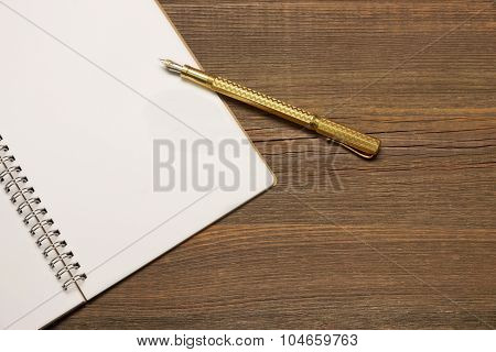 Notebook With Blank Page  And Golden Pen  On Wood Table